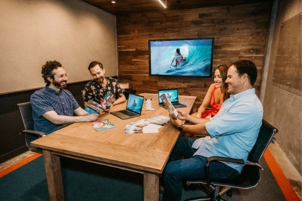 marketing team of 3 men and 1 woman sitting around a table discussing ideas